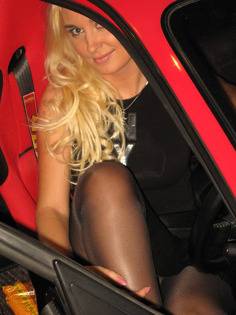 blonde car show model in red car