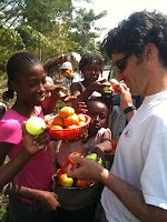 local Haitians from Port-au-Prince and Jacmel and a volunteer looking down at several bowls of fruit