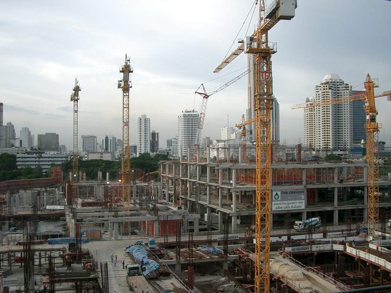 Building site scene concrete pillars cranes steel supports