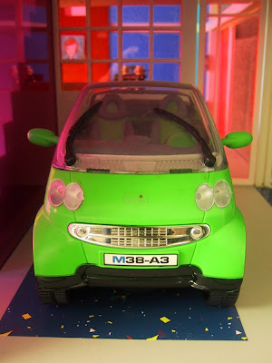 Modern miniature Kaleidoscope doll's house car port with Smart car.