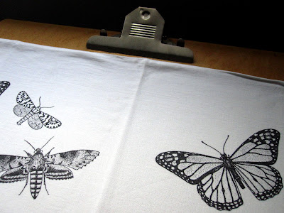 Art board covered with a pillowcase with butterflies printed on it.