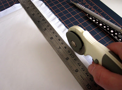 A rotary cutter, cutting along the edge of a metal ruler on a piece of white paper and fabric.