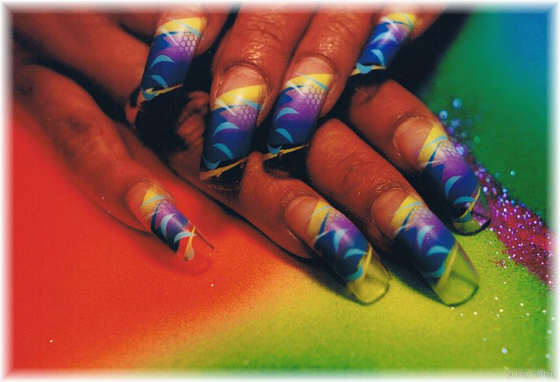 topnails: Long curved nails dressed up with purple, yellow and blue art