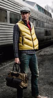 Homem com colete amarelo e bolsa de marrom com trem ao fundo. Viagem. Inesperada. Chegada, partida.