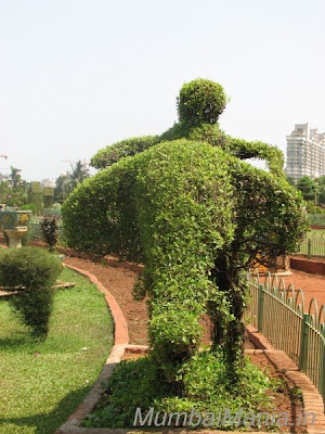 man on the elephant sculpture at Hanging Gardens