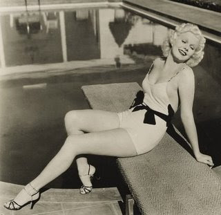 Jean Harlow striking a pose. Her suit is very glamourous for the time ...