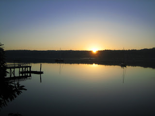 image of sunrise over a calm harbor, live on an island
