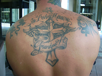 "Tattoo of wings behind it is graced by a banner that reads ""In Loving Memory"
