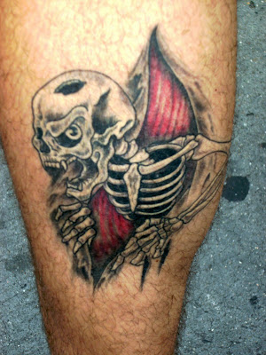 ripping skull and skeleton hands tearing through skin tattoo