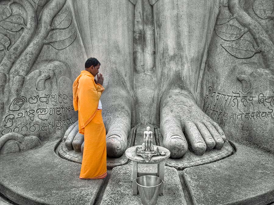 priest standing in front of gomateshwara statue and offering prayer