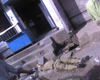 policeman lies drunk on road in Delhi, India