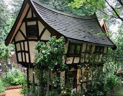 Сказочный дом возле аллеи парка. Зомик в зеленых растениях у лесной тропинки. Фото красив.