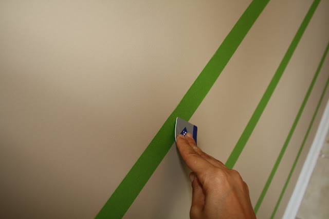 Using a credit card to smooth out painter's tape