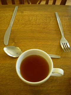 Cup of tea with knife, fork and spoon