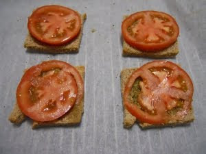 Poner una rodaja de tomate en cada loncha de pan.