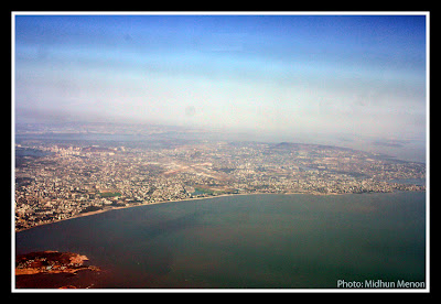 arial photograph of mumbai city scape with coastal line visible taken from aircraft window
