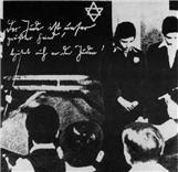 Joodse leerlingen worden vernederd ten overstaan van hun klasgenoten. Op het bord staat: Joden zijn onze grootste vijanden. Kijk uit voor joden!