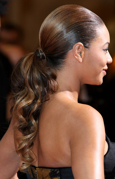 Slick pulled back with curly ponytail hairstyle.