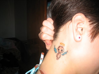Small angel tattoo behind ear.
