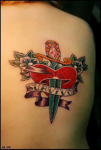 Heart and dagger with flowers tattoo.