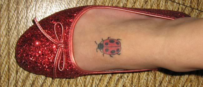 ladybug tattoo on top of foot.