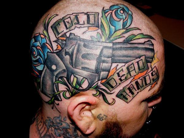 Head tattoo with gun and flowers.