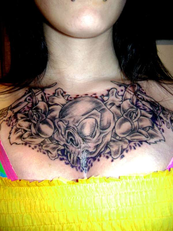 Skull and crossbones chest tattoo.