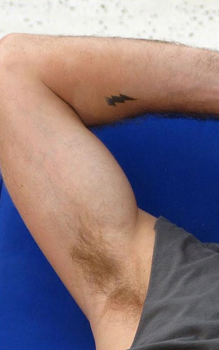Lightning bolt design on right arm, which may or may not by a real tattoo.