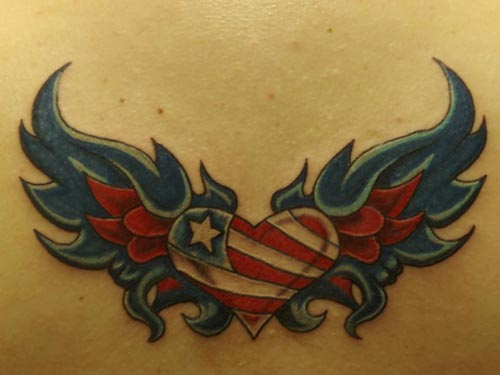 Red heart tattoo accessorized with thunder, flower and banner on