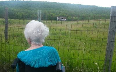 Mom looking down on her childhood home from the churchyard