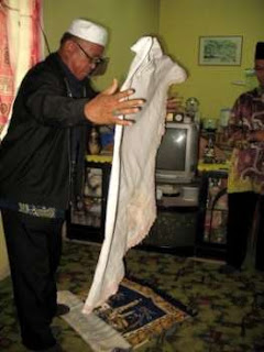 A religious affairs department official lifts the khimar and finds nothing inside.