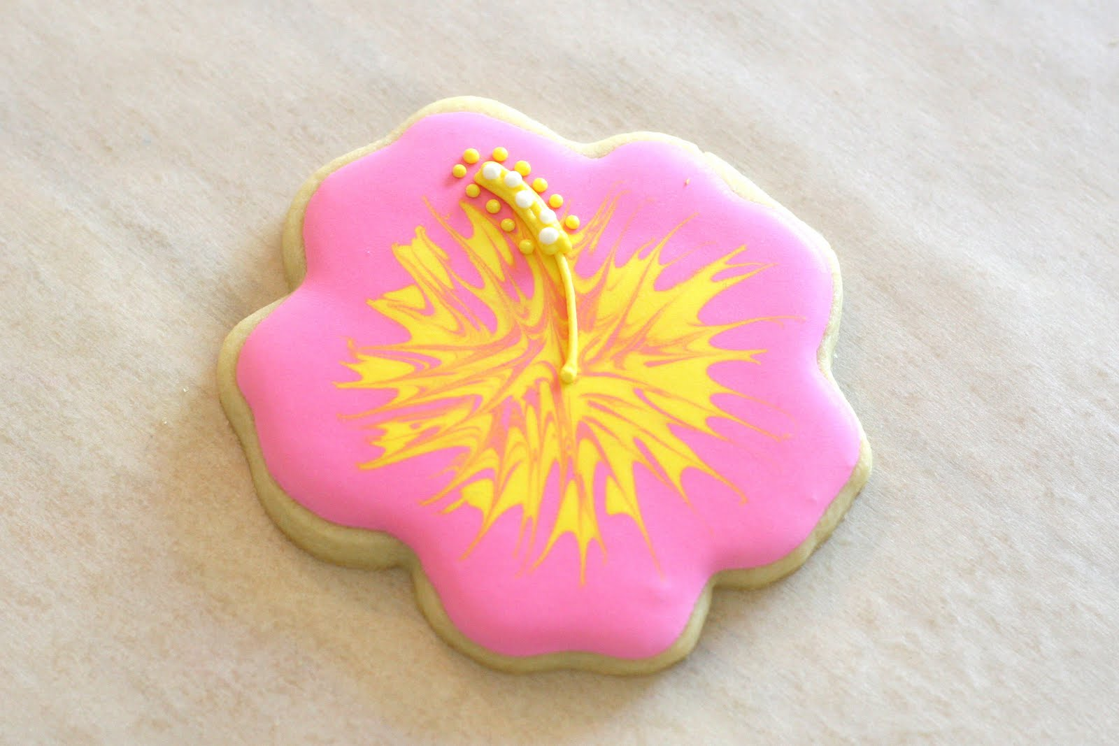 Cookie decorating how to make pretty hibiscus cookies glorious treats while the line and dots are still wet hold the cookie over a paper plate to catch the excess and sprinkle some yellow non pareils sprinkles on the end of izmirmasajfo