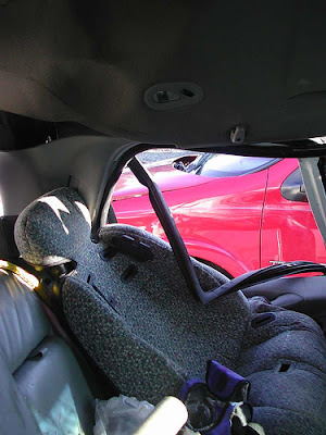 Empty car seat still in situ with roof, side panel, and window frame intruding.