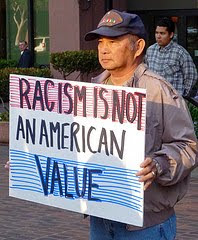 protester with sign that says Racism is not an American value