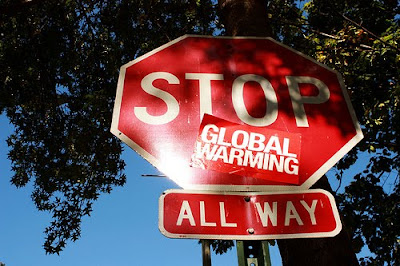 stop sign with sticker that says global warming under stop