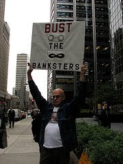 man with sign that says bust the banksters