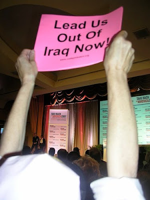 protester holding pink sign that says lead us out of Iraq now