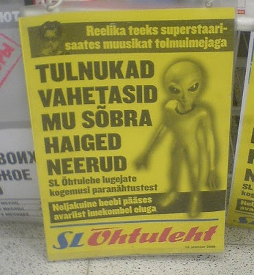 foreign tabloid newspaper with picture of space alien on it