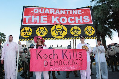 protest with two banners, Quarantine the Kochs and Koch Kills Democracy www.codepink.org