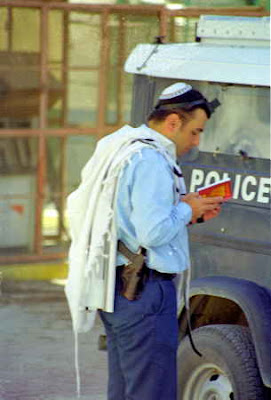 A beany..a shawl..an official car..a bible..and a gun...Must be a Rabbi..or a student with two jobs