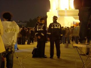 在大中至正門前吹著寒風也要執勤的警察,站在群眾外圍觀察現場狀況