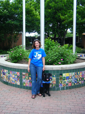 I'm standing with a black lab in working jacket, in front of a colorful round tiled planter with school flagpoles in the middle
