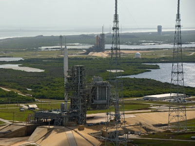 The Ares I-X flight test vehicle and space shuttle Atlantis sit on adjoining launch pads