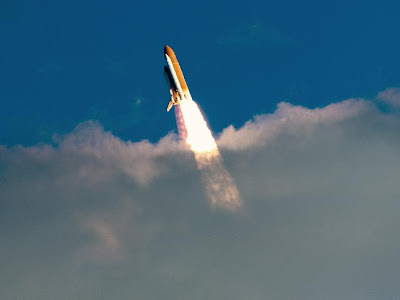 Space shuttle Atlantis breaks through the clouds during launch on its STS-129 mission