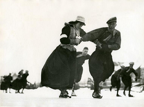 Skating arm in arm in traditional costume on Frisian skates (wooden skates) in Marken, the Netherlands. [1938]. Nationaal Archief / Spaarnestad Photo, SFA002002733