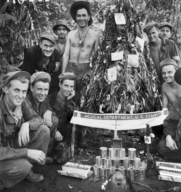 Buna, Papua, 1942. American soldiers at an advanced dressing station with a handmade Christmas tree decorated with surgical cotton wool and cigarette cartons.