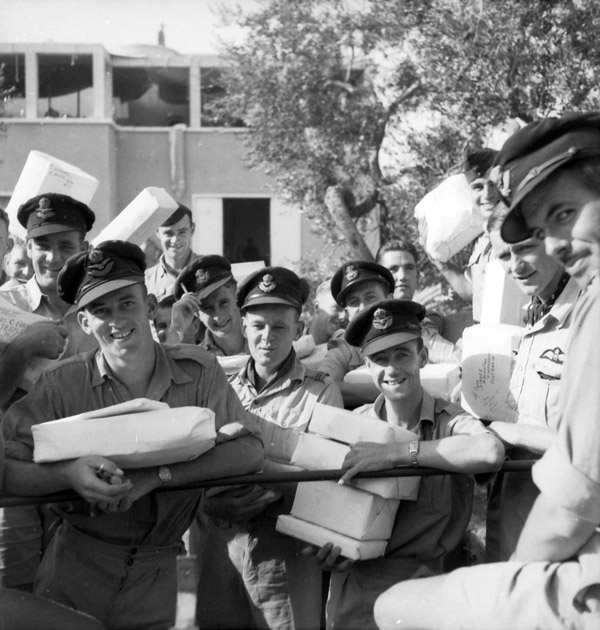 Christmas in Bari, Italy, 1943. Pilots of No. 3 (Kittyhawk) Squadron RAAF, on their way to the Army Post Office with parcels ready to catch the Christmas mail.