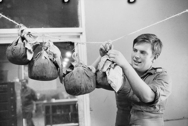 South Vietnam, 1971. Private (Pte) David McColl of Page, ACT, hanging puddings to mature before Christmas. Pte McColl spent his spare time during the weeks leading up to Christmas supplementing the supply of Christmas cakes and puddings provided by families and friends of soldiers still serving in Vietnam.