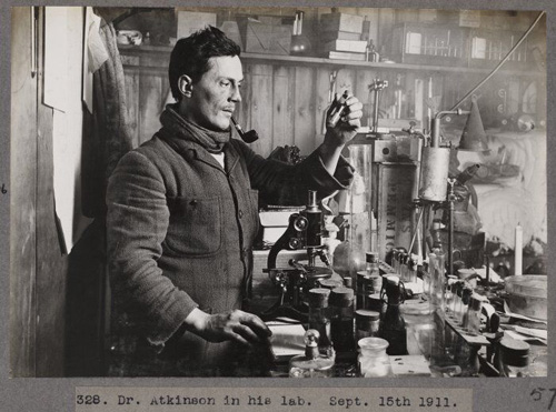 "Dr Edward Atkinson in his lab, photographed September 15th, 1911 by Herbert George Ponting during the British Antarctic (""Terra Nova"") Expedition (1910-1913). Shows him standing by a table of items, including a microscope, holding a test tube."