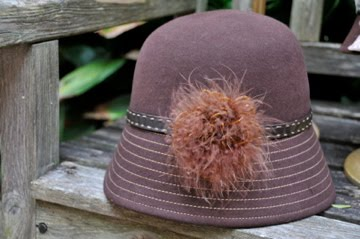 Brown stitched felt hat with feathers